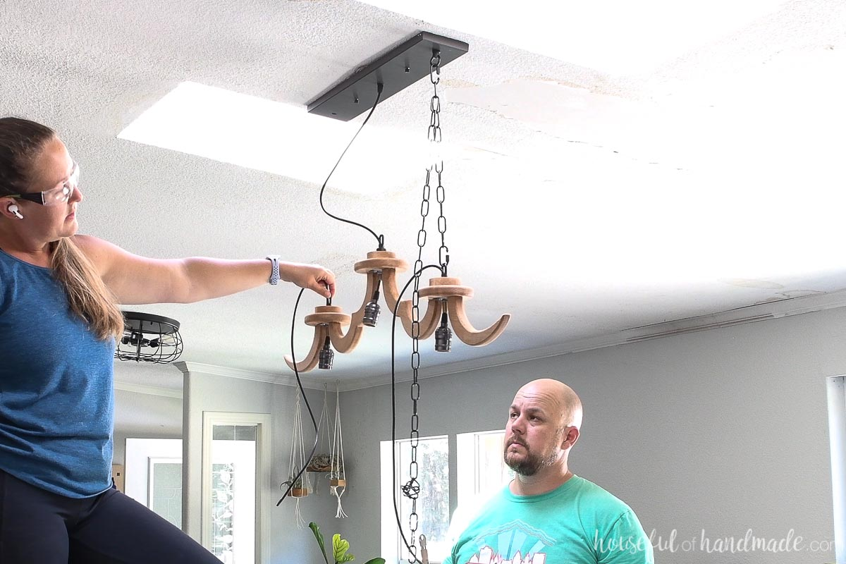 Holding up the DIY wood chandelier with the chain looped on one side looking at the height.