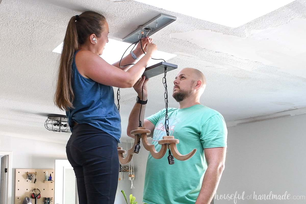 Attaching the wires from the DIY light fixture to the outlet box with wire nuts.