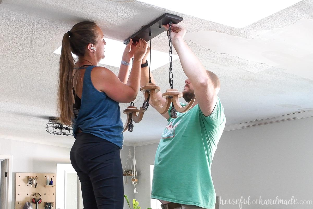 Securing the DIY chandelier to the ceiling box.