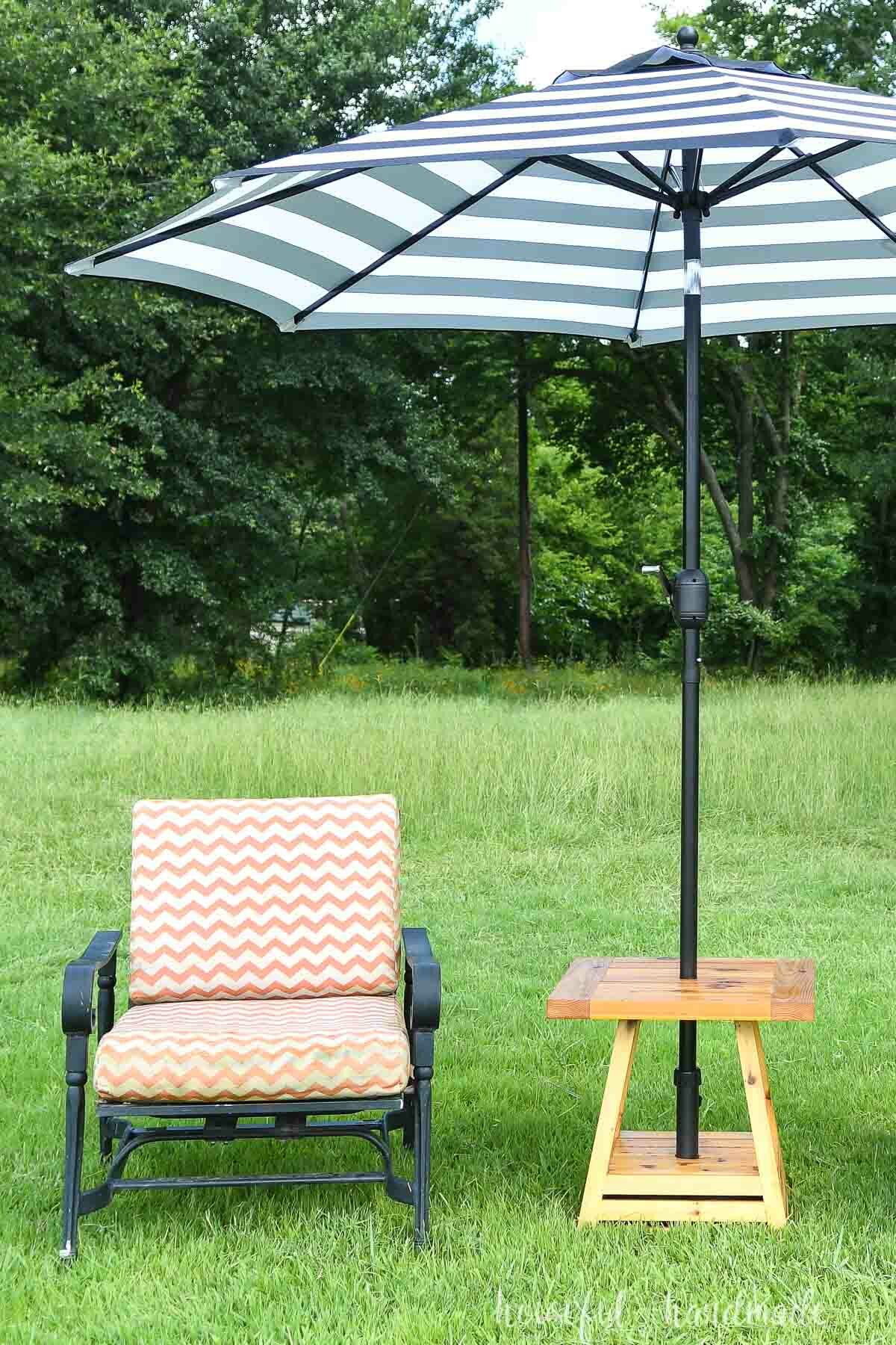 Umbrella side table set up on the lawn next to an orange and white cushioned chair.