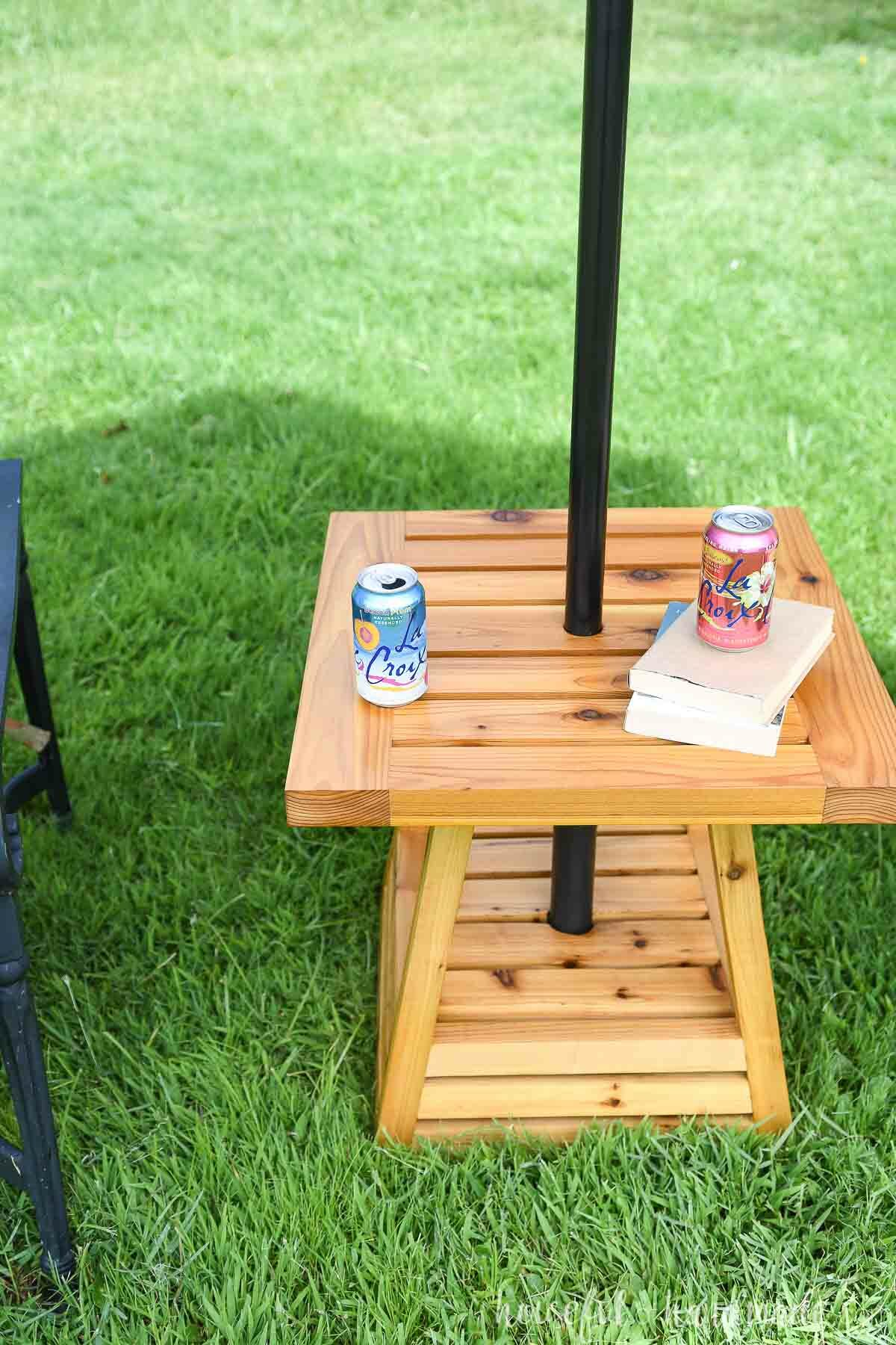 Looking down onto the top of the outdoor side table with a pyramid base and books and drinks on top of it.