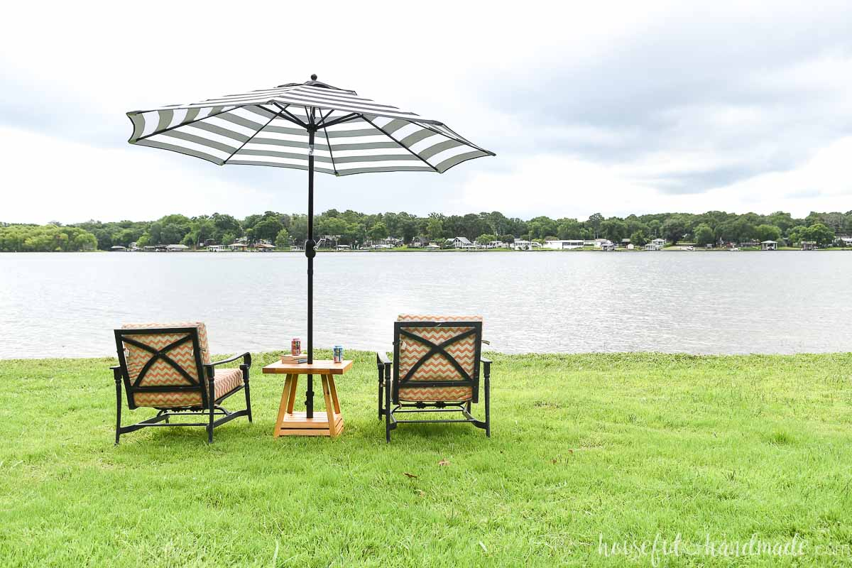 Two patio chairs sitting on each side of the umbrella side table overlooking a lake.