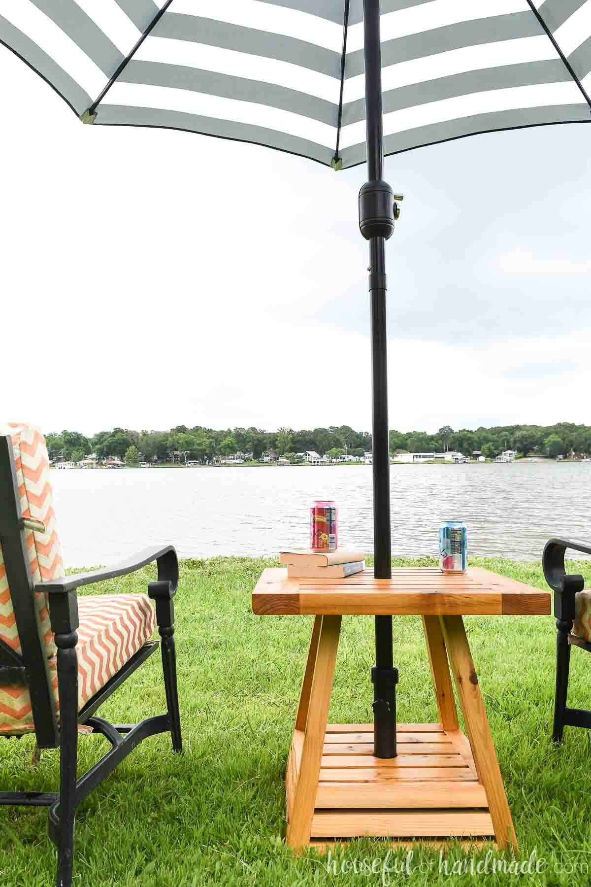 Umbrella side table with a black and white striped umbrella in it next to black frame outdoor chairs in front of a lake.