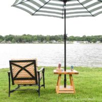 DIY umbrella side table with black and white striped umbrella in it and outdoor chair with cushions next to it looking over a lake.