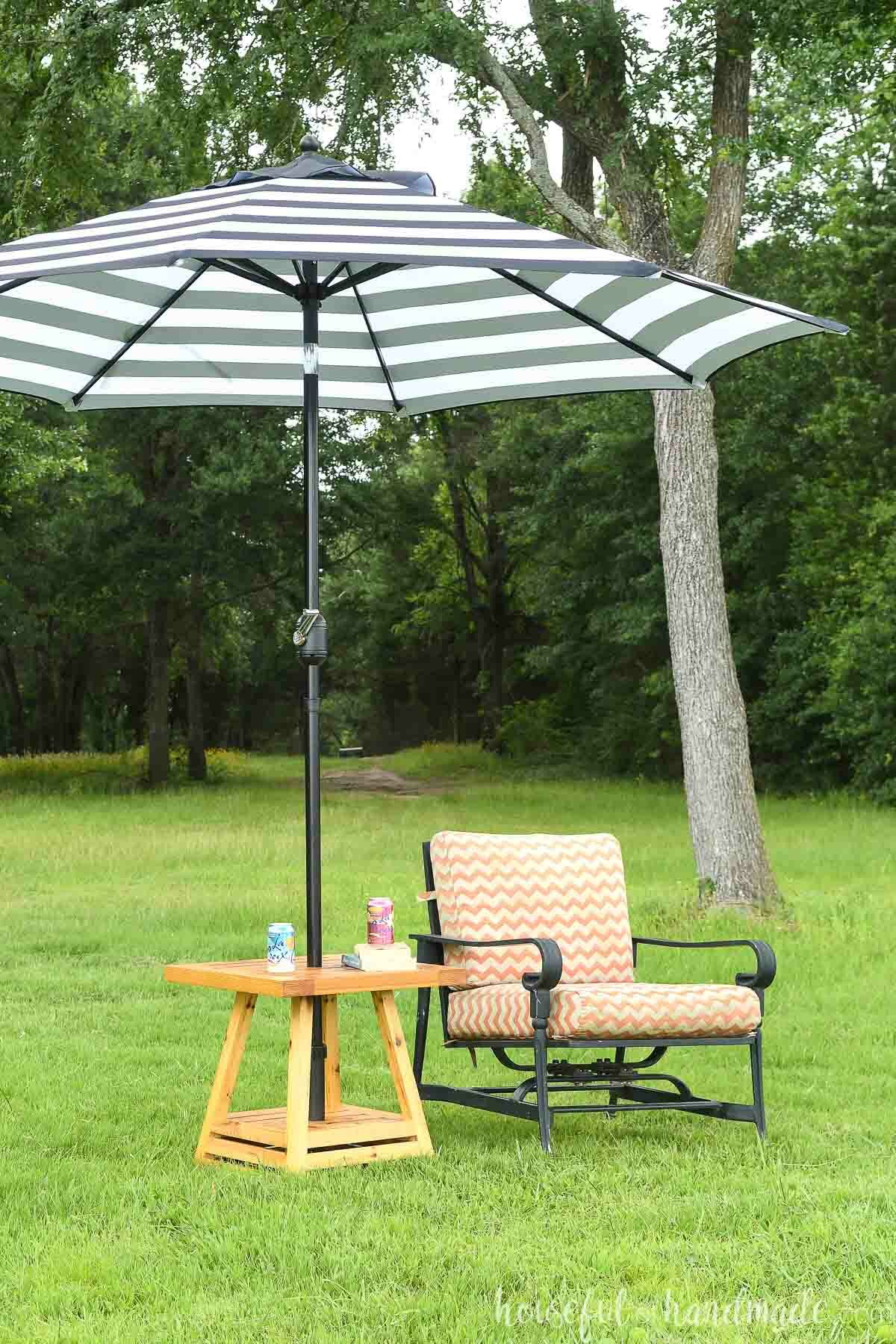Small outdoor umbrella table next to chair on a lawn with trees in the background.