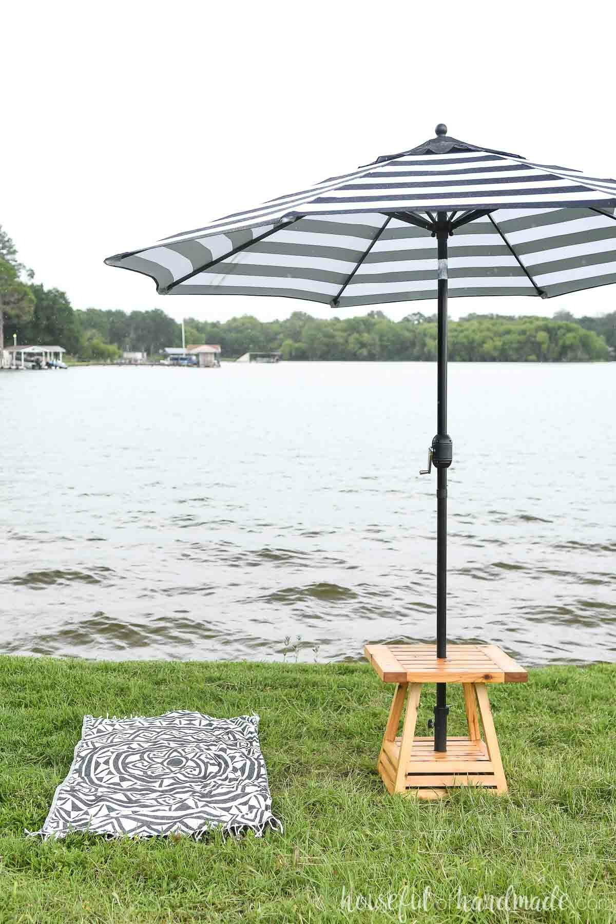 Small patio table with umbrella hole set up next to a beach towel by a lake.