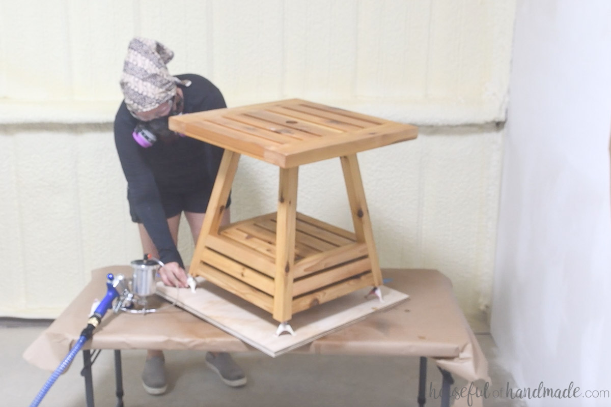Placing paint pyramids under each foot of the side table while spraying the finish.