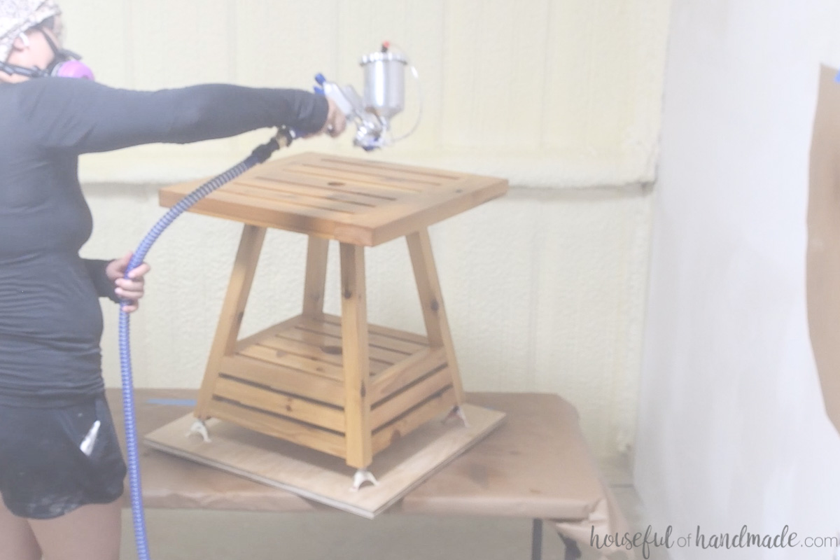 Spraying the Waterlox finish on the top of the side table.