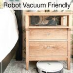 Picture of a white robot vacuum cleaning under a nightstand with text overlay: 11 Furniture Builds that are Robot Vacuum Friendly.
