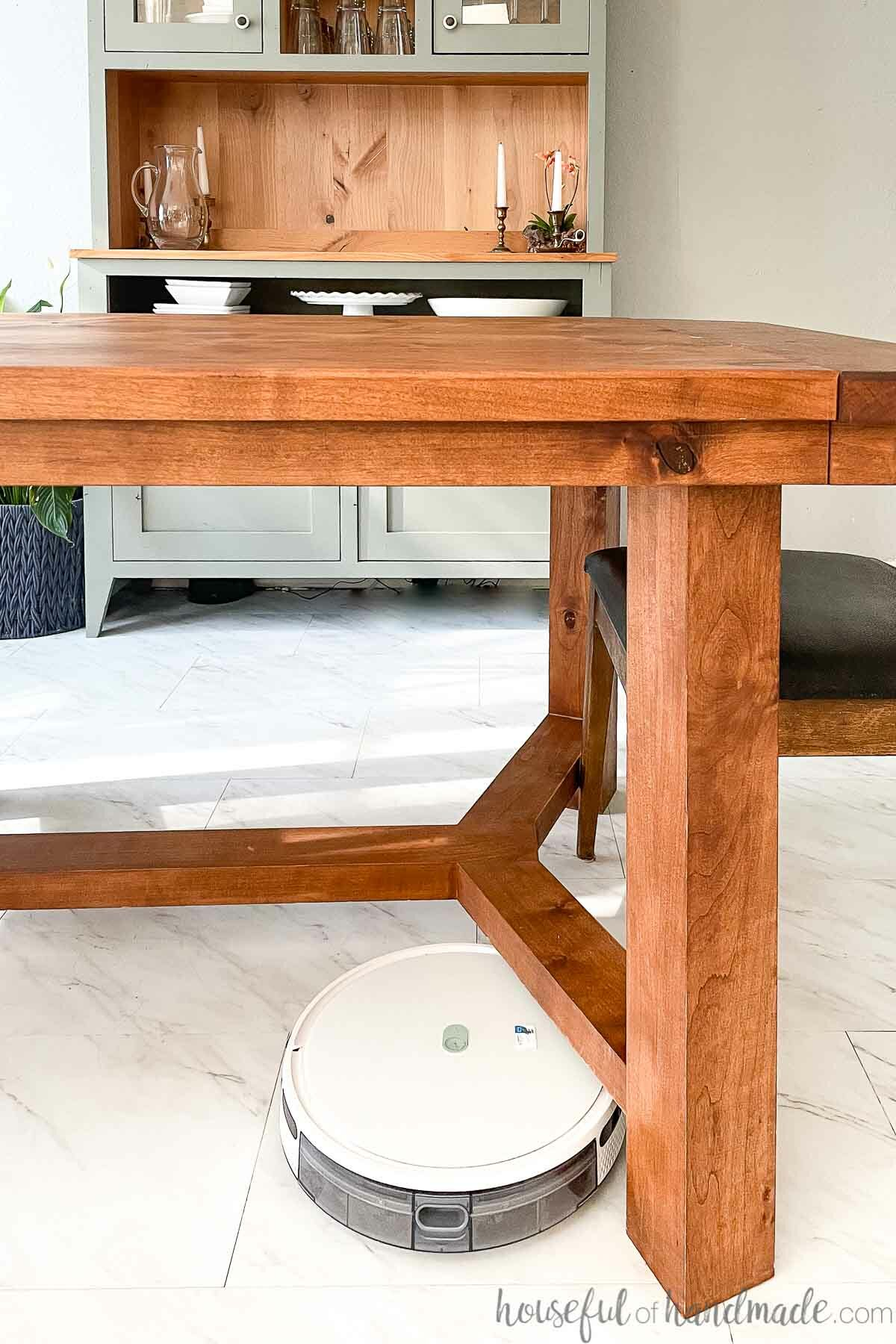 White Yeedi robot vacuum cleaning under a dining table made with enough clearance to make is robot vacuum friendly with a hutch in the background.