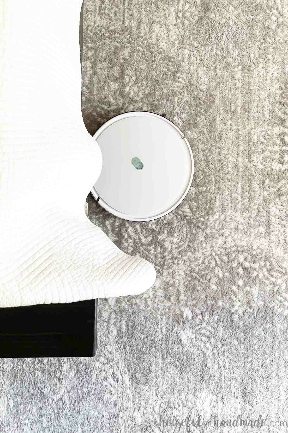Top down view of a white robot vacuum cleaning a rug under a bed.