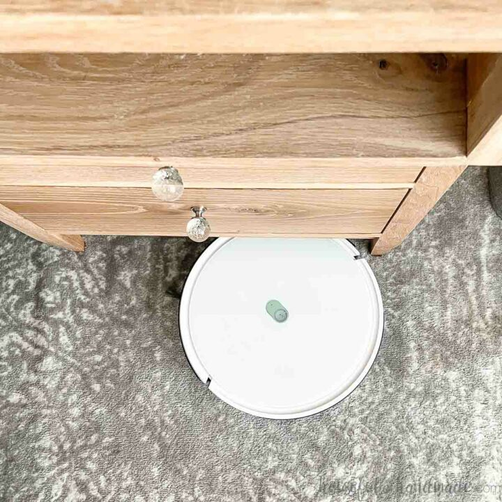 Looking down at the front of a nightstand with a white Yeedi robot vacuum cleaning the gray and white rug below it.