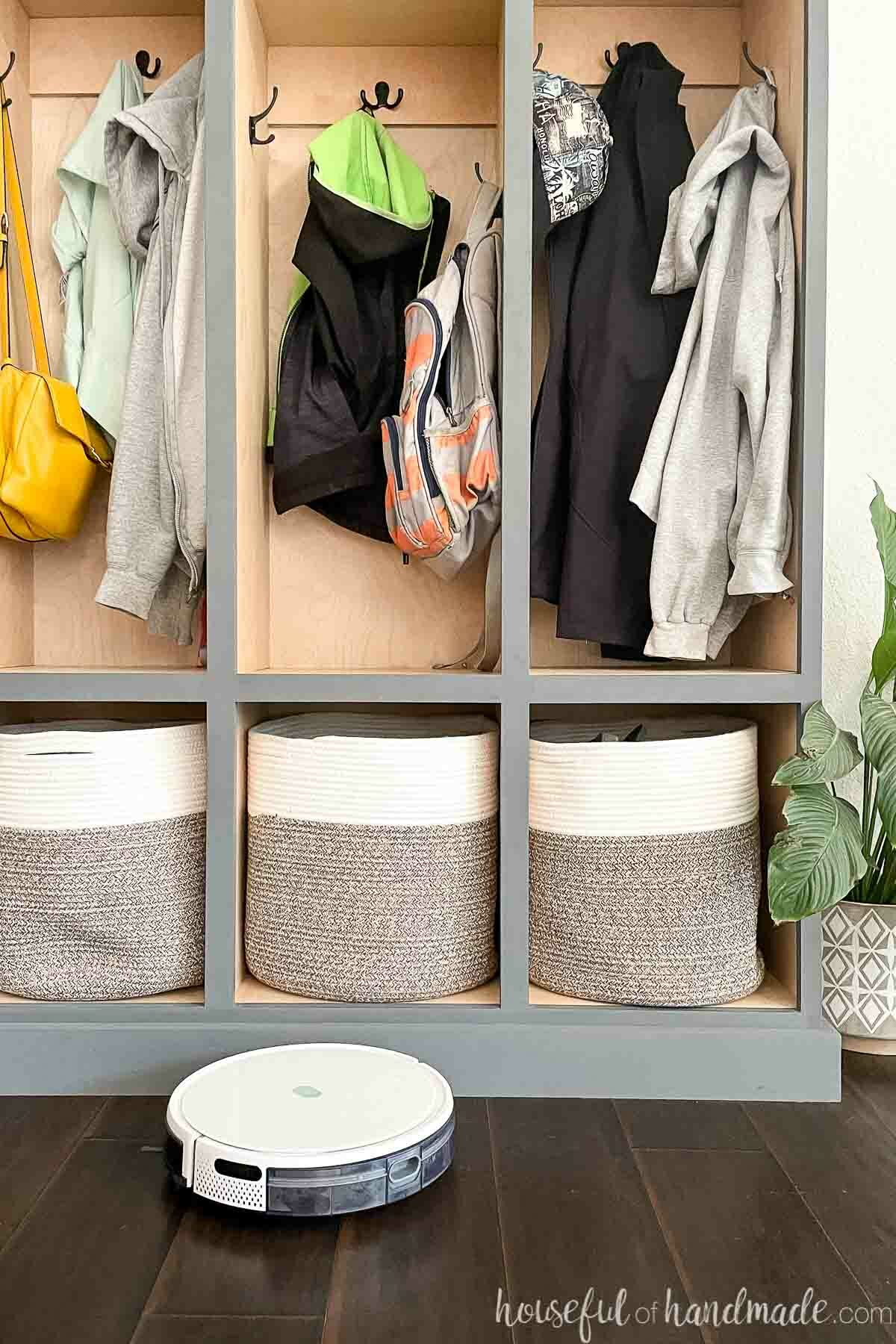 DIY mudroom storage lockers with robot vacuum cleaning around the base.