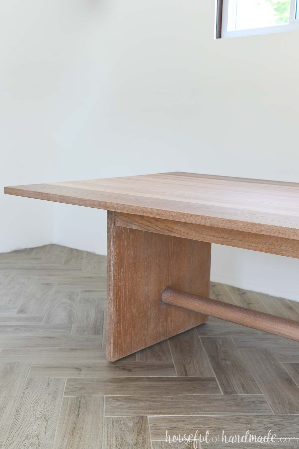 Close up of the one side of the refinished oak table top and leg with round center support.