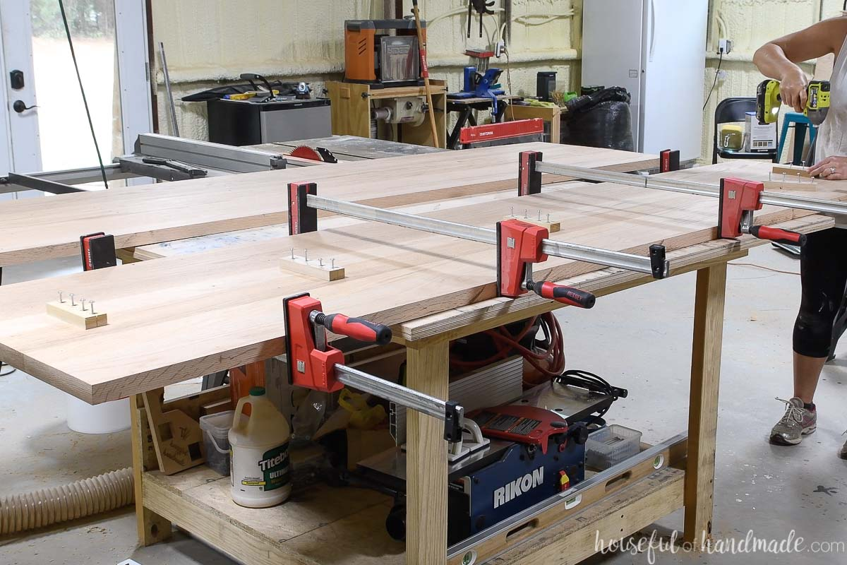 Two boards clamped together on a table with scraps of wood attached to the seams to hold them together.