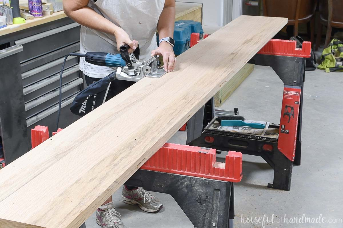 Adding biscuit slots to the table top board sitting on a sawhorse.