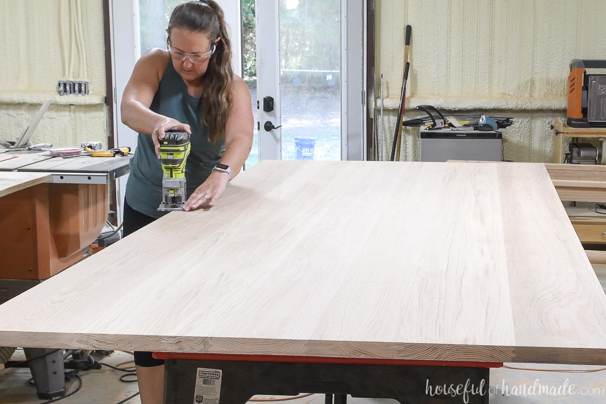 Adding a chamfered edge to the top edges of the table top with a palm router. .