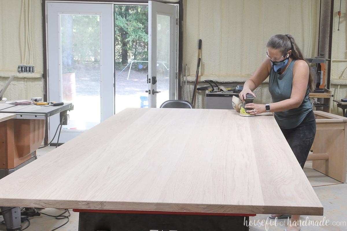 Sanding the final grit of the table top refurbish with an orbital sander.