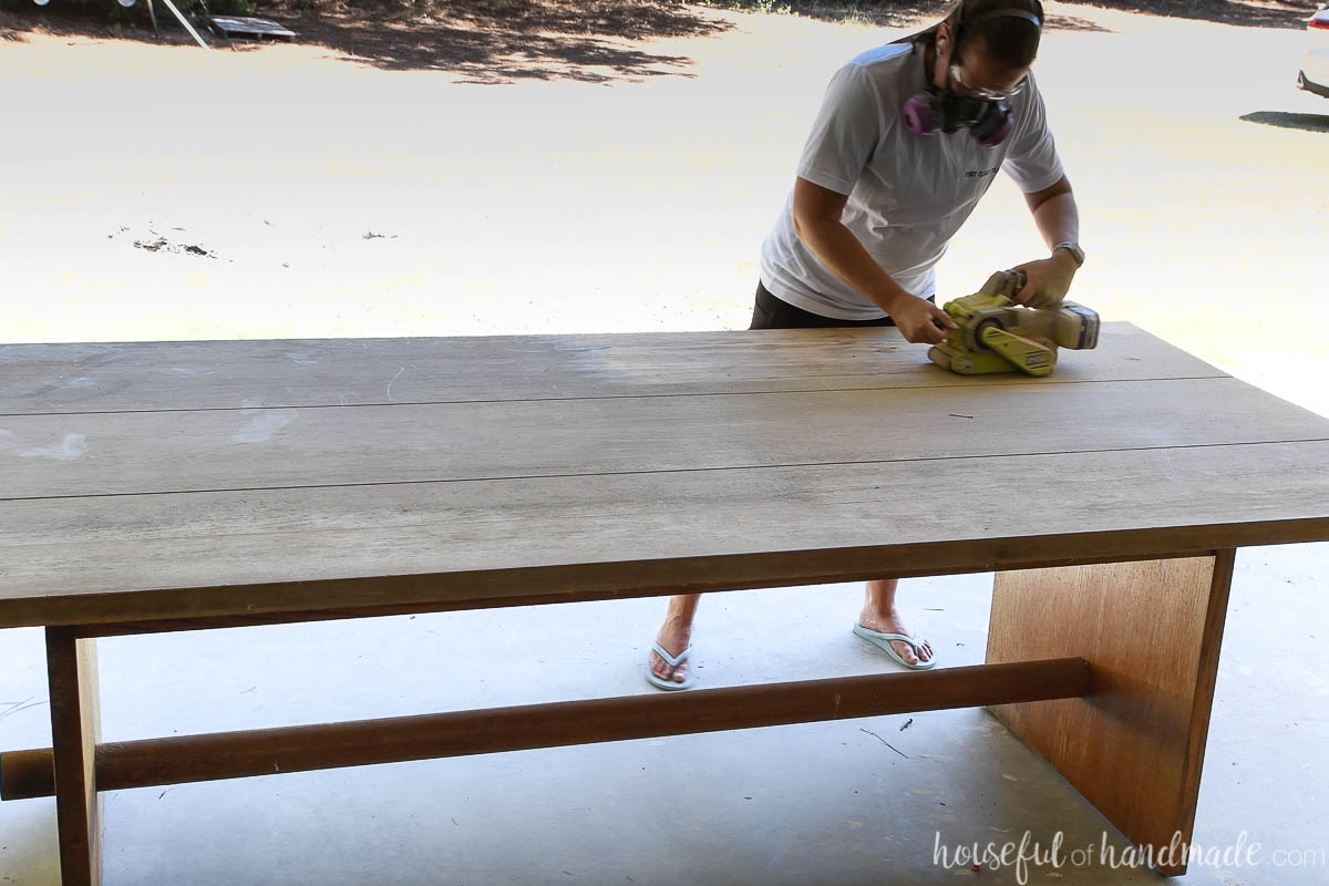 Sanding the top of an old oak table with a belt sander.