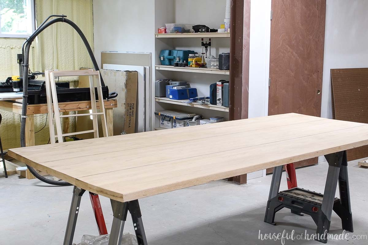 Bowed table top sitting on sawhorses after being sanded.